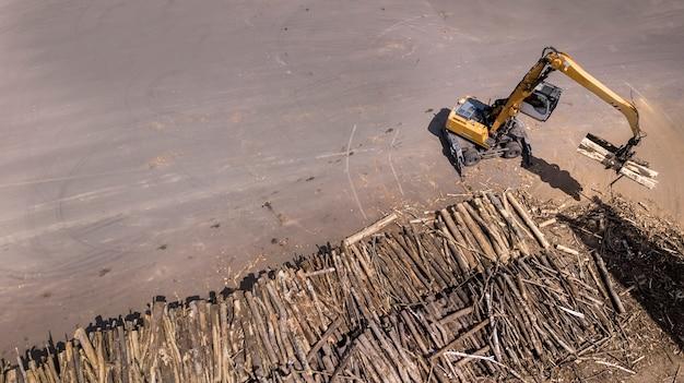 Погрузчик загружает деревянные балки в грузовик