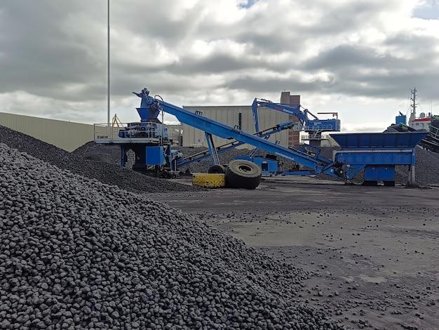 Погрузочно-разгрузочный комбайн для насыпных грузов насыпает уголь на балкеры у пристани порта