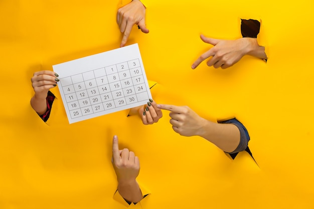 引き裂かれた黄色い紙、セール、ブラックフライデー、ショッピングのコンセプトを通してカレンダーを保持している多くの手