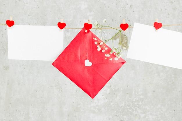 Любовное письмо висит на веревке и цветок на светлом фоне.