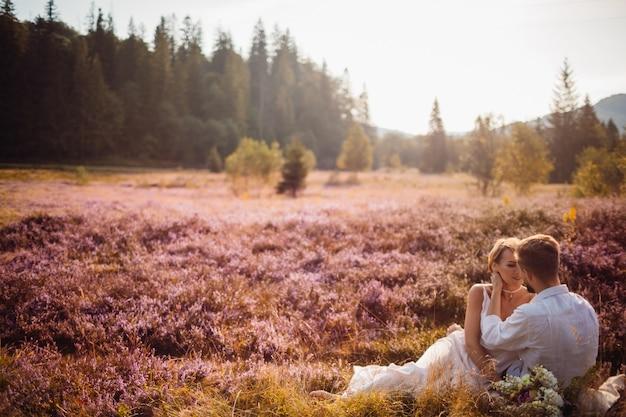 포용과 잔디에 앉아 사랑에 사랑스러운 커플