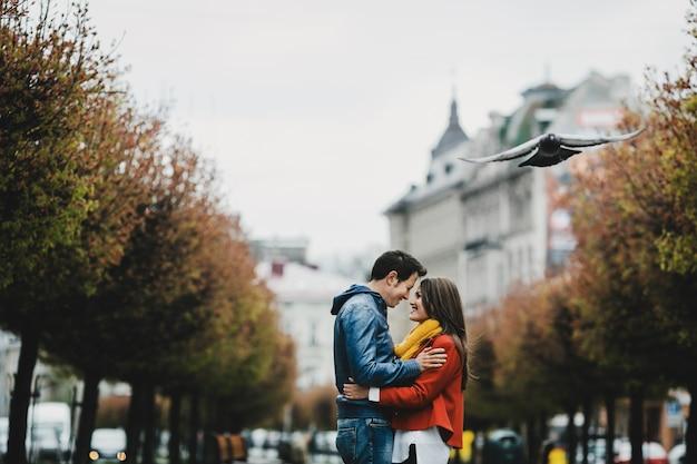 Прекрасная пара в любви охватывает и стоит на аллее