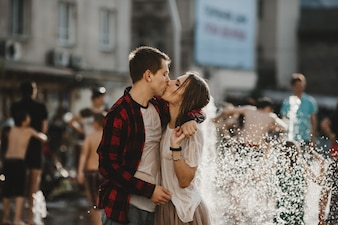 The lovely couple in love kissing  near fountain