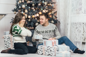 The lovely couple in love looking at presents