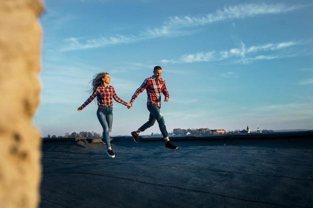 지붕을 따라 달리는 사랑에 빠진 사랑스러운 커플