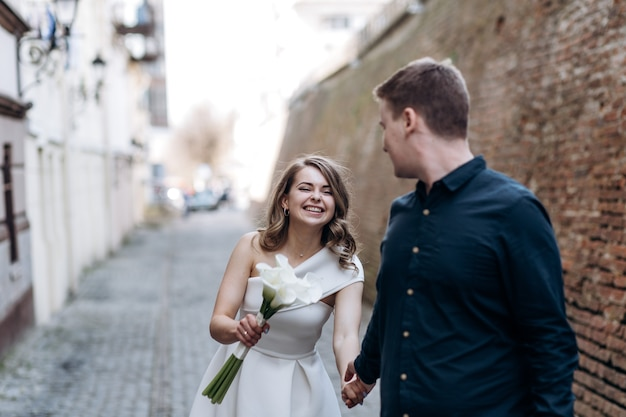 狭い通りを歩く愛の美しいカップル