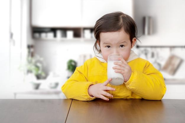 かわいらしい女の子は朝食をとり、スプーンでヨーグルトを飲んでいます