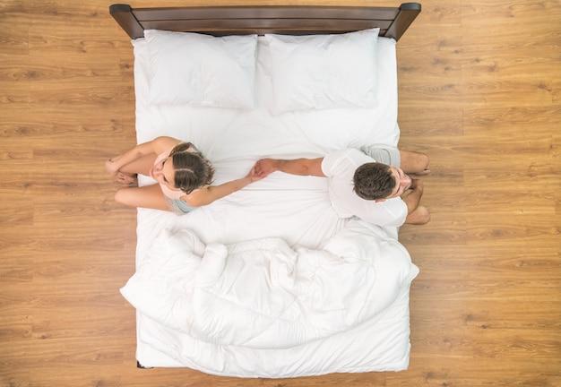 Влюбленные держатся за руки на кровати. вид сверху