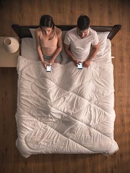 恋人たちはベッドと電話に座っています。上からの眺め