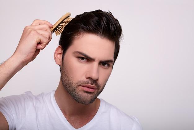 Роскошная брюнетка расчесывает свои густые здоровые черные волосы.