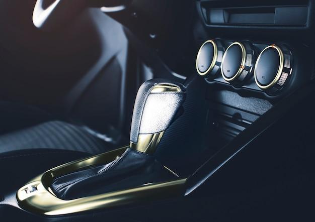 Роскошный рычаг переключения передач с хромированным золотом цвета автоматической коробки передач в роскошном автомобиле.