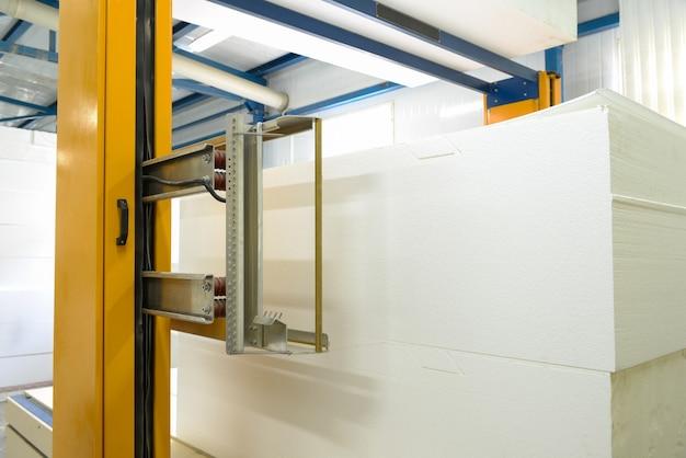 Станок режет пенопласт. завод по производству сэндвич-панелей из пенополистирола