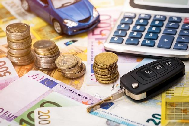 На банкнотах евро - автомат, ключи, монеты и калькулятор.