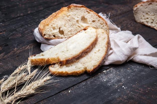 오래된 빈티지 나무 테이블에 있는 소박한 빵의 거시적 전망. 무료 텍스트 공간이 있는 어두운 변덕스러운 배경.