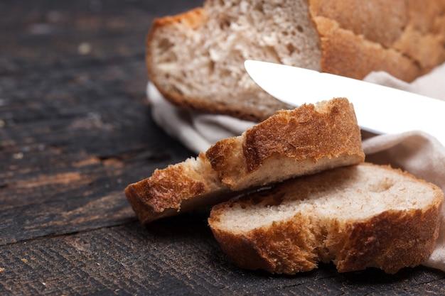 오래된 빈티지 나무 테이블에 있는 소박한 빵의 거시적 전망. 무료 텍스트 공간이 있는 어두운 나무 배경.
