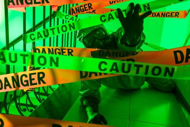 Безумный ученый в защитном костюме и противогазе прорывает запрещающие ленты «опасность» и «осторожно». нарушение карантина.