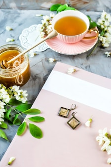 Журнал рядом с чашкой чая и банкой меда, среди цветущей акации