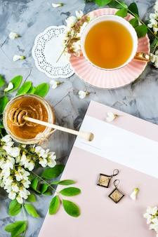 아카시아 꽃이 만발한 차 한 잔과 꿀 항아리 옆에있는 잡지