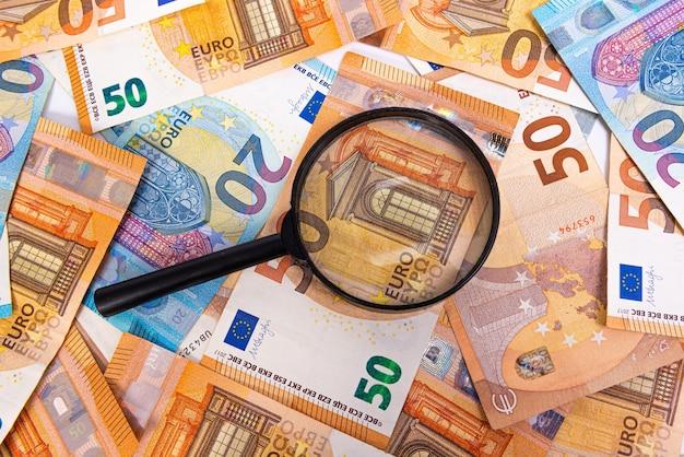 Увеличительное стекло, лежащее на пакете банкнот евро, крупным планом