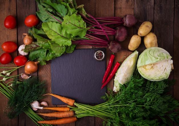 Основные ингредиенты - овощи для приготовления борща (свекла, капуста, морковь, картофель, помидоры). вид сверху