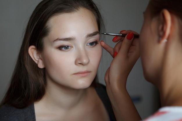 메이크업 마스터는 젊고 아름다운 소녀의 얼굴에 눈썹 모양을 모델링합니다.