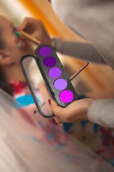 メイクアップアーティストは、ブラスでアイシャドウのセットを手に持って、女の子にメイクをします