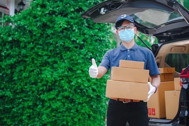 男性のアジアの配達スタッフがお客様の紙箱を保管していました。配達員は防護マスクと防護手袋を着用します。