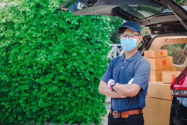 Мужской азиатский персонал доставки держал бумажную коробку или коробку клиента. работники службы доставки носят защитные маски и защитные перчатки.
