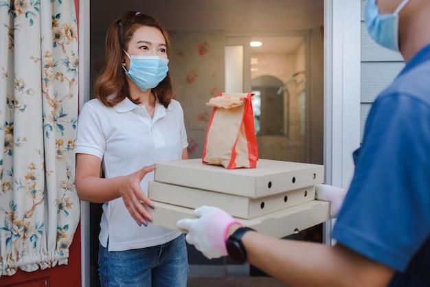 男性のアジアの荷主は、家の前にある美しい女性のクライアントに、フードデリバリーユニフォームに紙箱を入れて商品を配達しました。速達宅配サービスのコンセプト