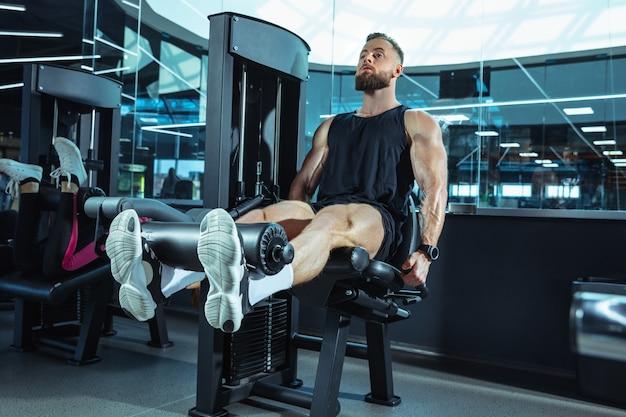 ジムで一生懸命トレーニングしている男性アスリート。フィットネスと健康的な生活の概念。