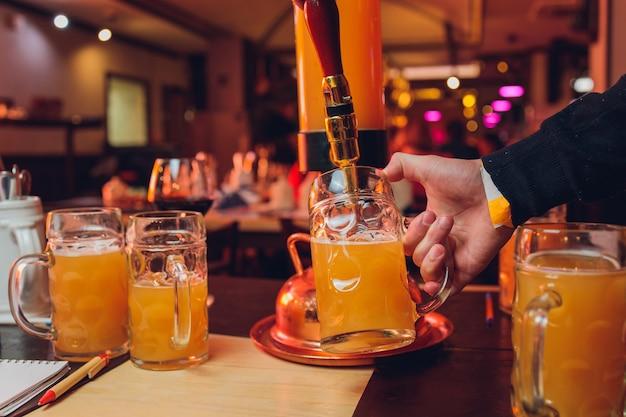 유리 클로즈업에 맥주를 붓는 남성 바텐더. 길거리 음식. 바텐더의 손에 시원한 맥주가 든 잔.