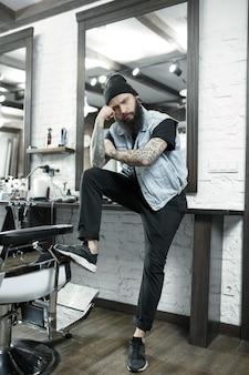 Мужской парикмахер на фоне парикмахерской. на руке мастера татуировка со словом бритье