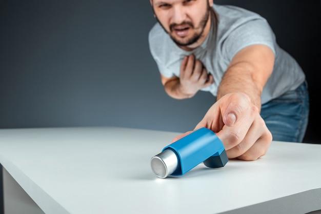 男性の手が喘息吸入器に到達し、喘息発作が起こります。気管支喘息、咳、アレルギー、呼吸困難の治療の概念。