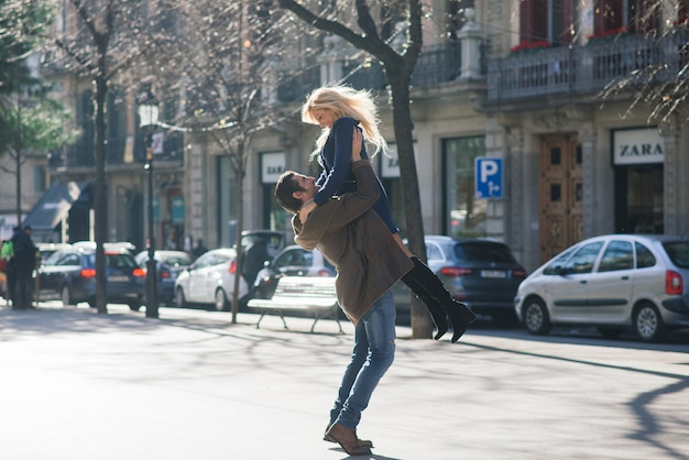 男性は妻の手を握り、優しく彼女を見つめ、街の通りを歩いています。