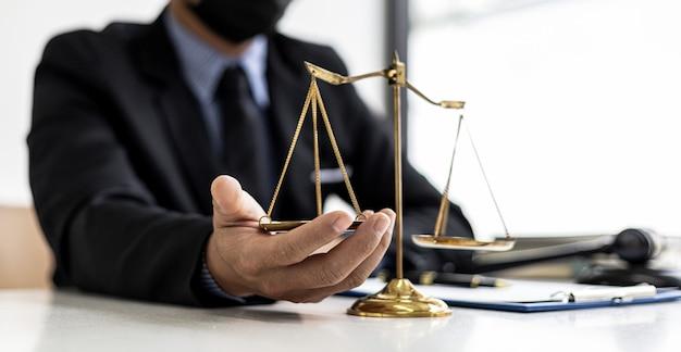 男性弁護士は自分の机の上の正義の尺度に秒針を置き、問題は正当化されなければならず、法律と人類に反してはならないと述べた。法学の概念。