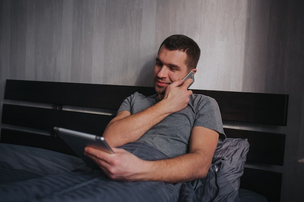 Модель-мужчина использует планшет и телефон одновременно. мужчина в постели утром. работа на дому.