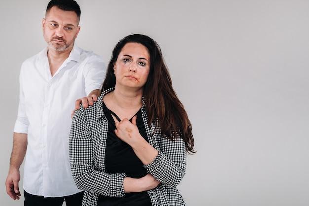 남성 강간범은 회색 배경에 구타당한 여성의 어깨에 손을 얹었다. 가정 폭력.