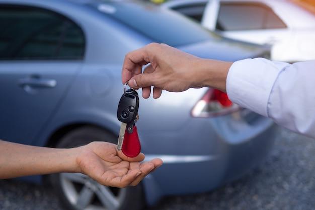 Продавец-мужчина отправляет ключи и машину покупателю после того, как согласился купить и продать машину. концепция проката автомобилей