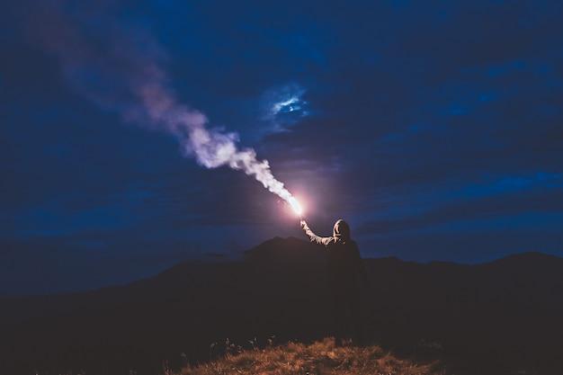 Мужчина стоит с палкой фейерверка на ночной горе