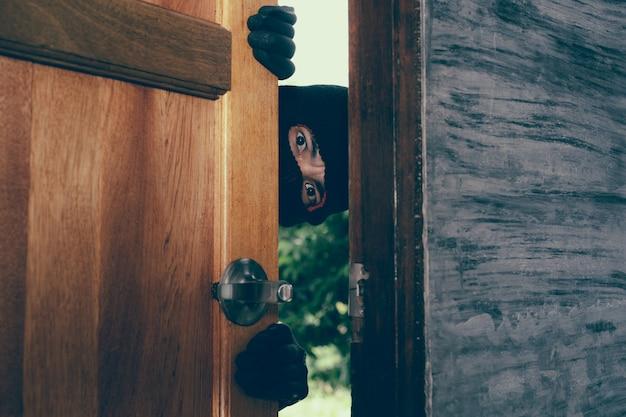 남자 도둑이 집 문에 나타났습니다.