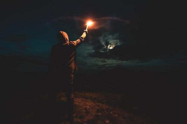 Самец с яркой фейерверковой палкой стоит на ночной горе