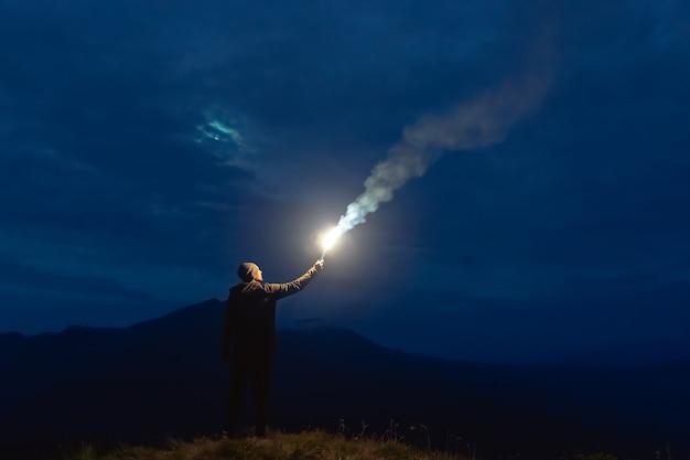 Мужчина с фейерверком стоит на горе. ночное время
