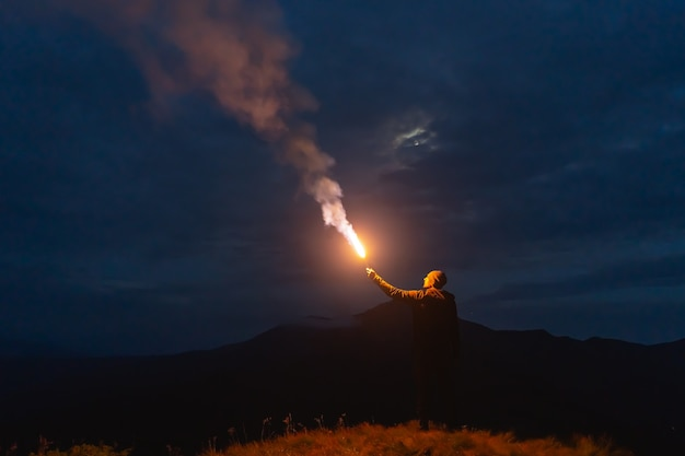 Мужчина с палкой фейерверка стоит на горе