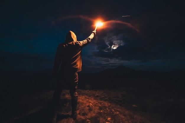 Мужчина с палкой фейерверка стоит на ночной горе