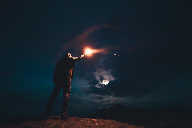 Мужчина с палкой фейерверка стоит на ночных горах