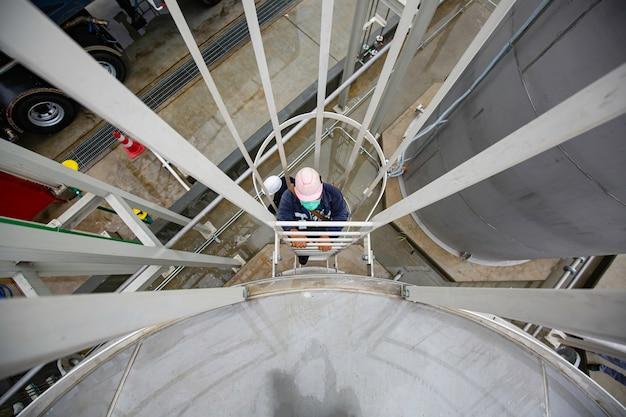 사다리 아래에 있는 남성 작업자는 스테인리스 스틸 탱크 저장 탱크 화학 메탄올 검사를 위한 것입니다.
