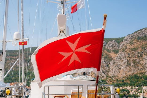 깃대에있는 몰타 국기는 산을 향한 요트를 타고 바람에 날아갑니다.