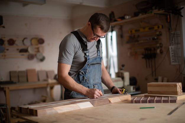 男-大工は木の測定を行います。