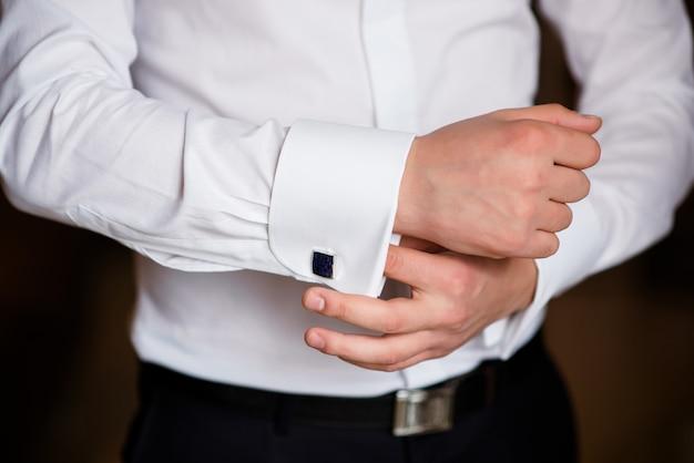 男は白いシャツに袖を合わせます。