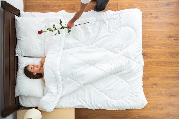 ベッドで朝食をとっている男性と女性。上からの眺め